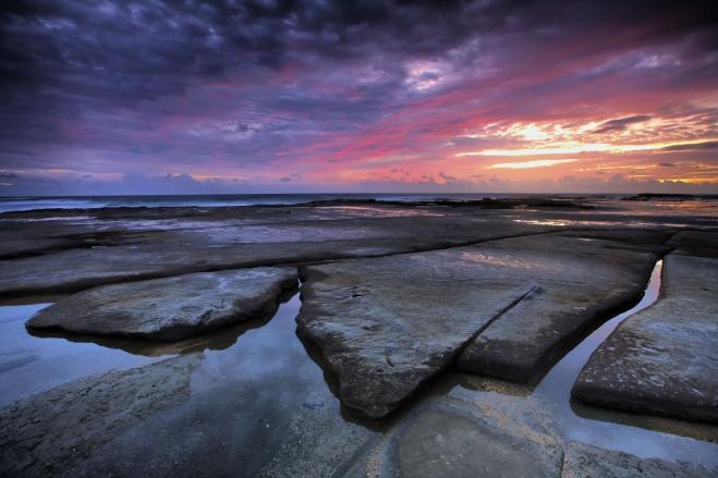 sun rising on the rocky sea wallpaper