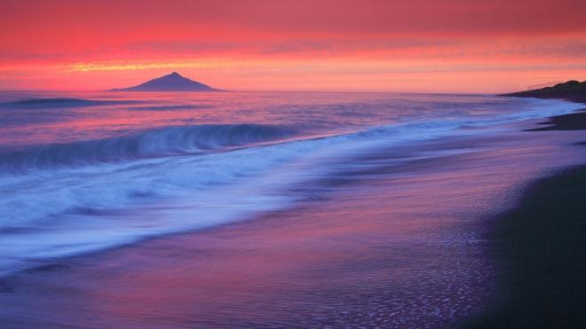 sun rising behind the blue sea wallpaper